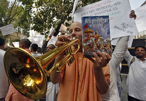 A member of the global Hare Krishna sect plays a trumpet during a protest outside the Russian consulate in Kolkata