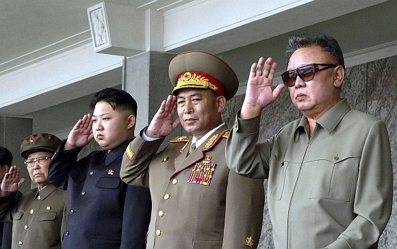 Kim Jong-il (right) and his son Kim Jong Un (third from right) salute as they watch soldiers attending a military parade in the Kim Il Sung square in Pyongyang in this September 9 photo