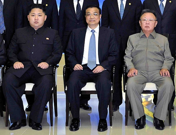 Kim Jong-Un and Kim Jong-il pose for photographs with the visiting Chinese Vice Premier Li Keqiang during their meeting in Pyongyang on October 24