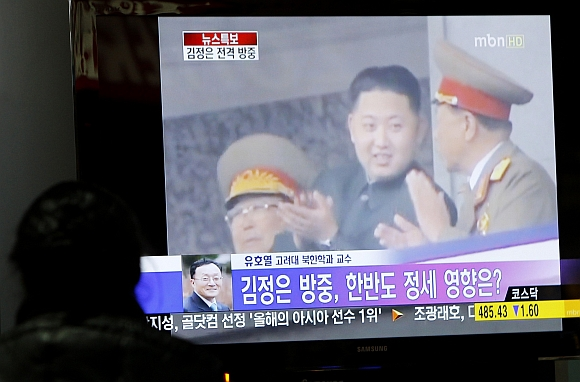 A man watches a television news regarding Kim Jong-un's sudden visit to China at the Seoul railway station in Seoul on May 20
