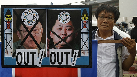 An anti-North Korea activist holds a North Korean flag and portraits of Kim Jong-il and his son Kim Jong-Un during a protest in central Seoul