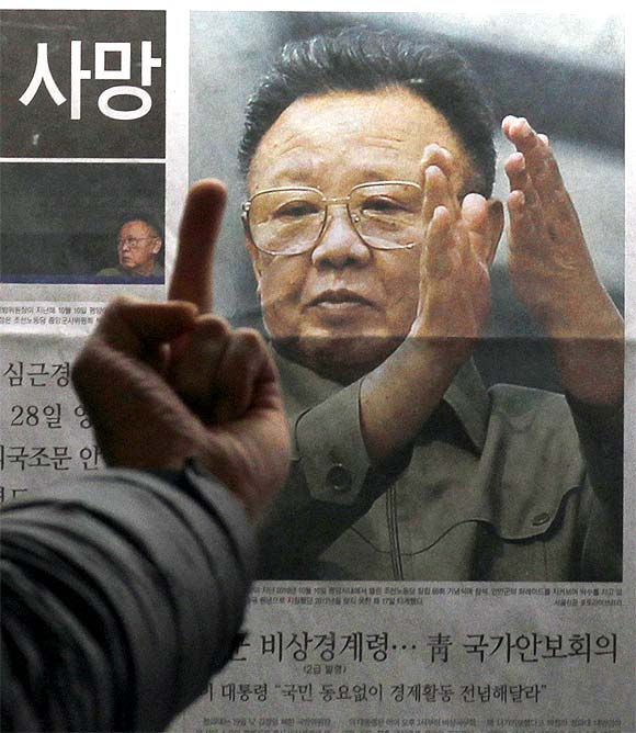 A man reacts at a picture of North Korean leader Kim Jong-il as he reads the reports of his death on the newspaper company's display b