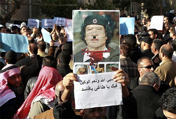 A protester holds up a poster of Libyan leader Muammar Gaddafi defaced as Adolf Hitler during a demonstration
