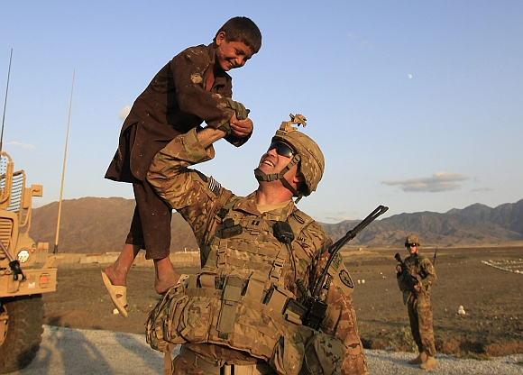 US military officer CPT Heiliger from Alpha Co, 2nd Battalion 35th Infantry, Task Force Cacti lifts a boy while on patrol in a village near Combat Outpost Penich in Khas Kunar district in Kunar