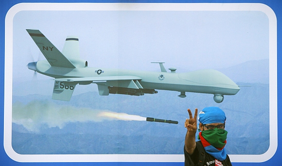 A Jamaat-e-Islami supporter flashes the victory sign in front of an image of drone, during a rally against drone attacks