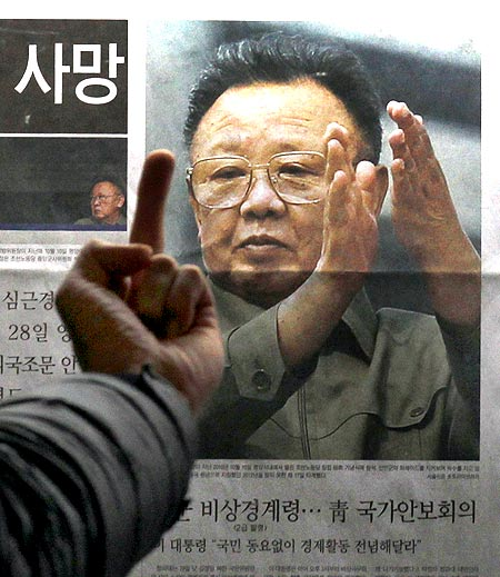 A picture of North Korean leader Kim Jong-il as he reads the report of his death on the newspaper company's display board in Seoul