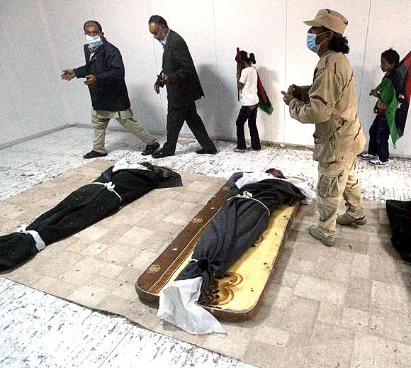 Libyans visit the body of slain leader Muammar Gaddafi inside a storage freezer in Misrata