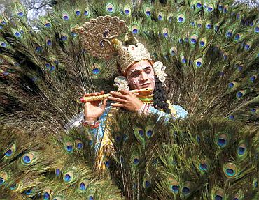 An artist dressed as Hindu Lord Krishna performs during the media preview