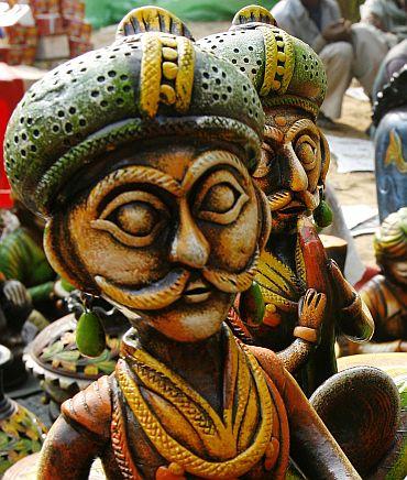 Labourers sit near a stall of sculptures at the Surajkund Crafts Fair