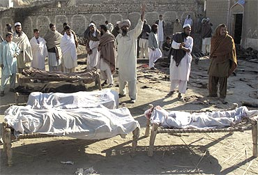 Villagers stand beside bodies of blast victims, near the site of a suicide bomb attack, in the town of Lakki Marwat in Pakistan
