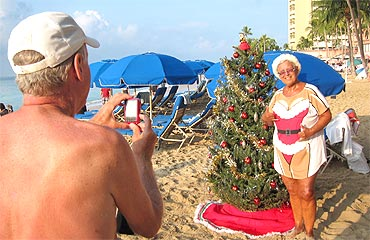 An American tourist in a Santa t-shirt poses for a photo in front of a Christmas tree