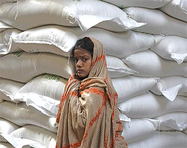 A Pakistani girl leans against sacks of sugar as she awaits handouts from customers at a wholesale market in Karachi