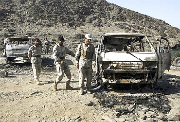 Afghan border police keep watch next to burnt vehicles belonging to a team of Afghan deminers who were kiddnapped by the Taliban