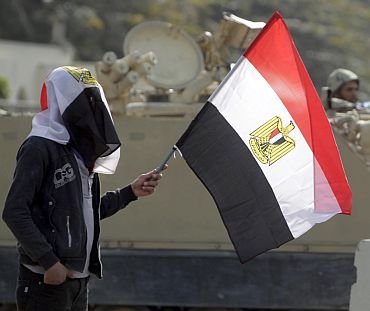 A supporter of Egyptian President Hosni Mubarak holds an Egyptian flag in front of an Egyptian army vehicle during a d
