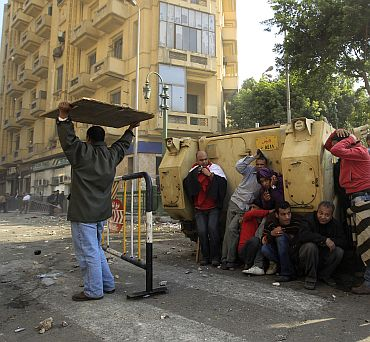 Demonstrators take cover during rioting between pro and anti Mubarak supporters