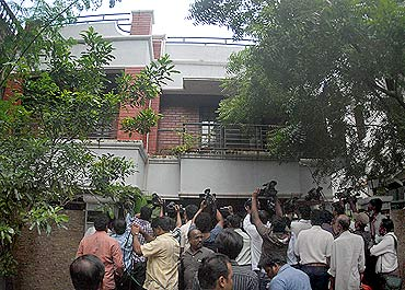 Television cameramen fight for space outside the residence of Sadiq Basha, an associate of A Raja