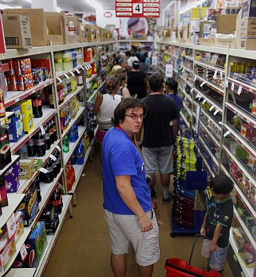 Shoppers queue to buy last minute supplies in a supermarket