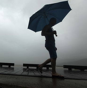 A sightseer walks along the waterfront in the northern Australian city of Cairns