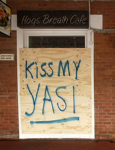 A hand painted board protects the front window of a cafe in the northern Australian city of Cairns