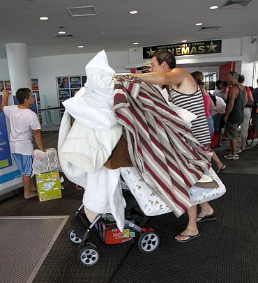 A man wheels bedding into an emergency cyclone shelter at a shopping mall