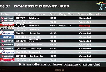 A flight information screen shows all flights cancelled except one at the Cairns airport