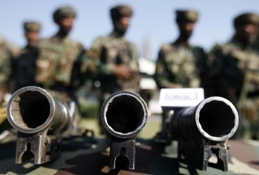 Army soldiers stand behind seized grenade launchers after a gunbattle with militants