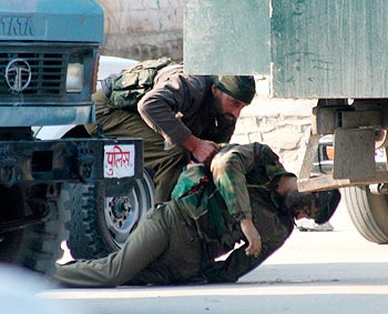A policeman lifts the body of a slain colleague during an encounter with militants in Srinagar