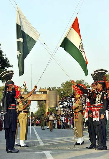 Pakistani Rangers and Indian Border Security Force lower their respective country flags during the daily parade at the Pakistan-India joint check-post at Wagah border