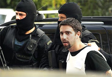 Policemen escort a terror suspect in Athens, who is charged with participating in a terrorist group and with illegal possession of explosives and weapons