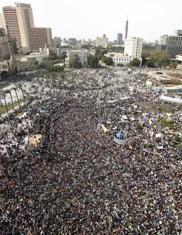 Opposition supporters gather and listen to Egyptian-born cleric Sheikh Yusuf al-Qaradawi, who says President Hosni Mubarak must stand down and leave Egypt, before Friday prayers at Tahrir Square