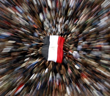 Anti-government demonstrators with an Egyptian flag shout anti-Mubarak slogans after Friday prayers at Tahrir Square in Cairo