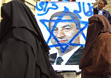 Women walk past an opposition supporter holding a poster of Egyptian President Hosni Mubarak