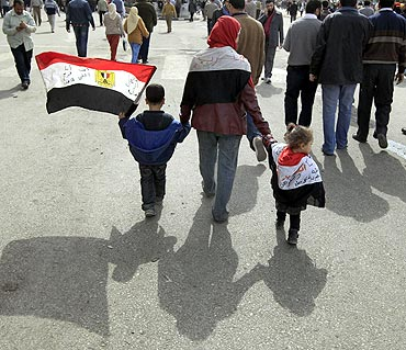 An opposition supporter walks with children to Friday prayers in Tahrir Square in Cairo