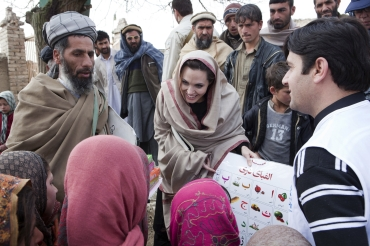 UNHCR Goodwill Ambassador Angelina Jolie presents education material to a local head teacher in a village outside Kabul