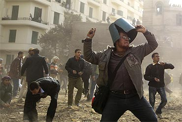 An opposition demonstrator throws a rock during rioting with pro-Mubarak supporters near Tahrir Square in Cairo