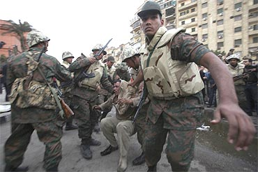 A pro-Mubarak supporter apprehended by opposition demonstrators is led away by the army during rioting near Tahrir Square in Cairo