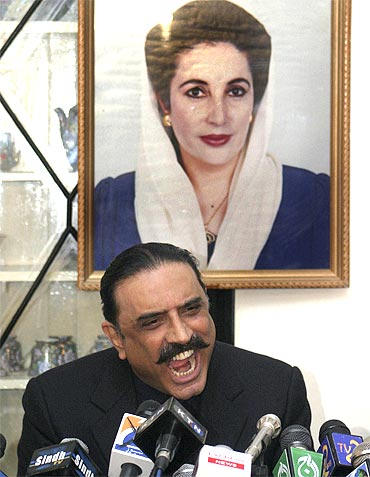 Zardari addresses a press conference in front of a photograph of his slain wife Benazir Bhutto