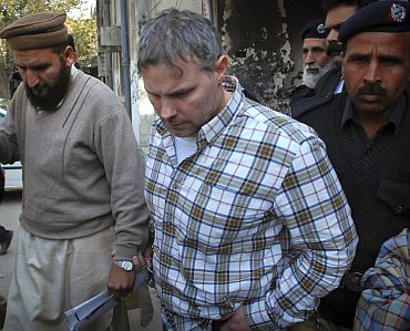 Raymond Davis is escorted by police and officials out of a Pakistani court