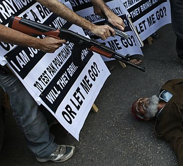 Supporters of a political party pose with masks and point toy guns at a man on the ground, as he pretends to be dead, during a protest against Raymond Davis