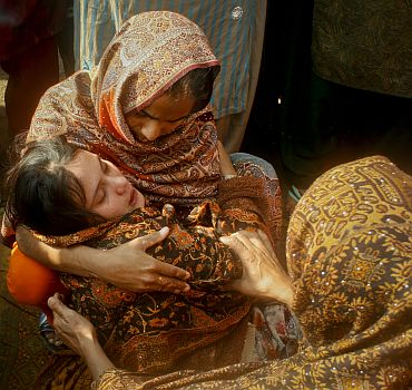Family members comfort the sister of Shumaila, who committed suicide after her husband was killed
