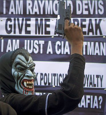 A supporter of a political party poses with a mask and toy gun during a protest against Raymond Davis