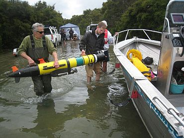 Dan Fornari (left) and Robin Littlefield, of Woods Hole Oceanographic Institution, load a REMUS autonomous underwater vehicle onto a support boat prior to launching the AUV on an eight-hour mapping and data capture mission