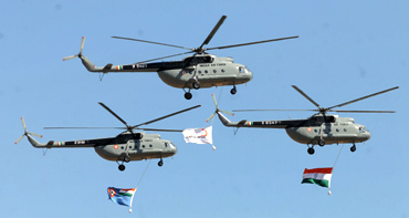 Indian Air Force helicopters fly before the start of display at Aero India 2011