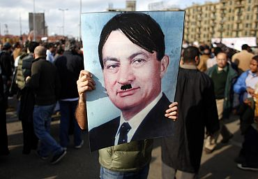 A protestor carries a picture depicting Mubarak as Adolf Hitler