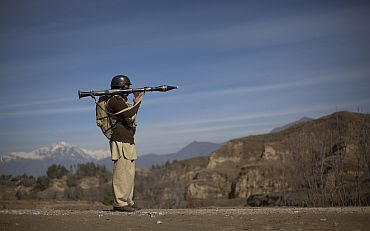 A Pakistani soldier holds a rocket launcher while securing a road at Khar in Pakistan's FATA region