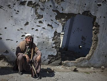 A member of the local Lashkar sits with his weapon next to a wall damaged in recent fighting in Khar