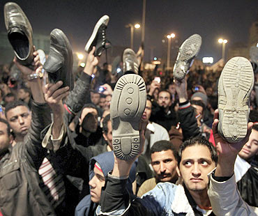 Anti-government protesters in Cairo's Tahrir Square wave shoes in dismay as President Hosni Mubarak speaks to the nation