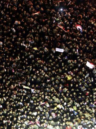Anti-government protesters in Cairo's Tahrir Square listen as President Hosni Mubarak speaks to the nation on Thursday