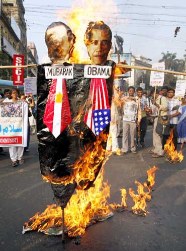 Activists from the Socialist Unity Centre of Indiaburn an effigy depicting Mubarak and Obama during a solidarity rally in Kolkata