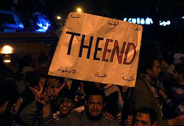 Anti-government protesters carry a placard and celebrate in Tahrir square in Cairo